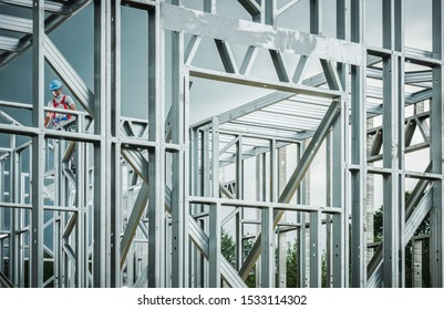 Steel House Frame Development. Caucasian Construction Contractor Wearing Safety Harness Working on the Frame.