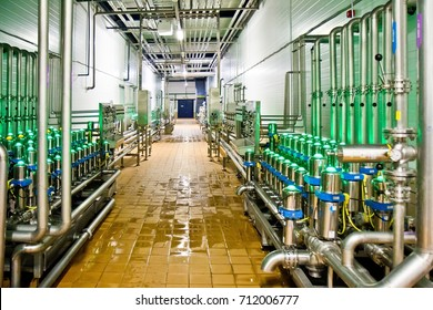Steel indicators of the beer production line in a bright room with spilled liquid on the floor