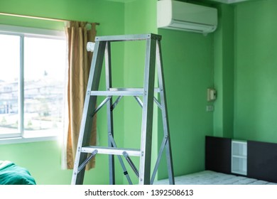 Steel ladder used by the worker to climb up to close to the air conditioner.