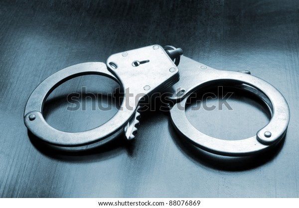 Steel metallic handcuffs on wooden table