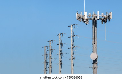 Steel monopole cell phone antenna array. Row of metal electricity utility poles in background. Blue sky background. Room for text.