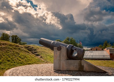 Steel mortar gun made in Obukhovsky Steel Foundry (diameter 205 mm, model of 1877) on the rampart of the Daugavpils fortress. Heavy, dark stormclouds and Latvian flag on the pole on the background.
