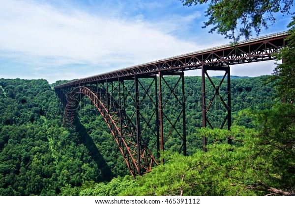Steel multicolored arch bridge stretching across the New River in West Virginia