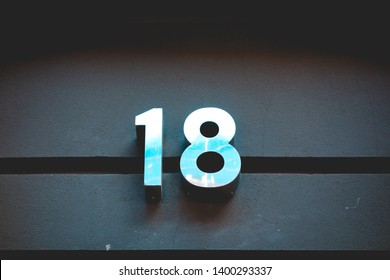 steel number 18 door sign on darken background