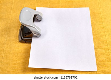 Steel office hole puncher is punctured by blank sheet of paper, yellow background.