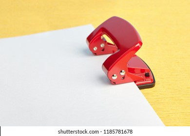 Steel office hole puncher red with white blank on yellow background, mockup with copy space.