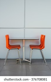 steel orange chairs and table in the middle