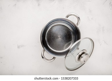 Steel pan and glass lid close-up on a white background. top view copy space