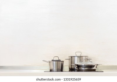 Steel pan, stewpot and stewpan standing on kitchen stove, kitchen utensils background with blank space for a text