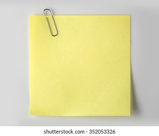 Steel paper clip and Yellow paper on white background