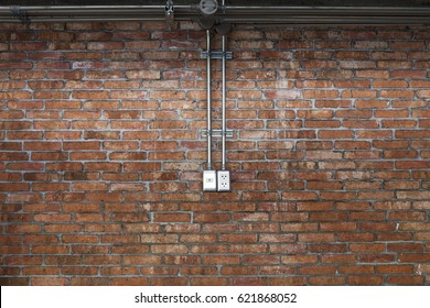Steel pipe electric wire and plug on vintage brick wall background