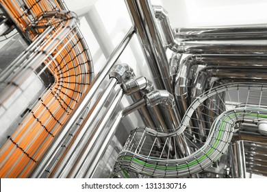 Steel pipelines and cables in factory interior as chemical industry background concept