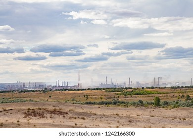 steel plant in russia autumn steppe with smoking chimneys on horizon under dramatic clouds