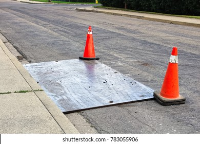 A steel plate on the road with construction pylons.
