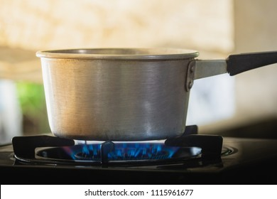steel pot on the gas stove with burning in kitchen