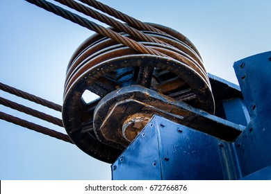 Steel pulley wheel with three steel cables looping around the pulley.