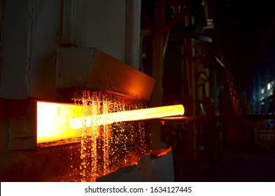 Steel quenching at high temperature in industrial furnace at the workshop of a forge plant. Process of cooling, heat treatmen. Blacksmith and metallurgical industry, steelmaking, hot rolling mill