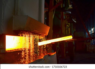 Steel quenching at high temperature in industrial furnace at the workshop of a forge plant. Process of cooling, heat treatmen. Blacksmith and metallurgical industry, hot rolling mill. Small sharpness