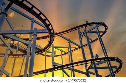 Steel rails for driving roller coasters in circular motions, on background evening sky and sun shining, concept relaxation and holiday of fun excitement and extreme activity in open air.