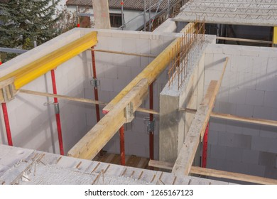 Steel raw posts and yellow wooden beams for prefabricated concrete parts of the upper floor ceiling