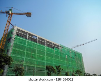 Steel scaffolding around the building for construction And green safety netting to control dust and items that may fall into the bottom of the safety control concept in high rise buildings