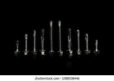 Steel screws on black background