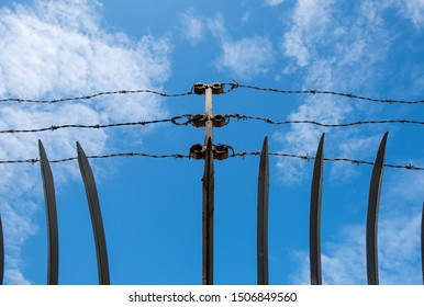 Steel security fence with spikes and cloud background. Barbed Wire isolated security perimeter fence.