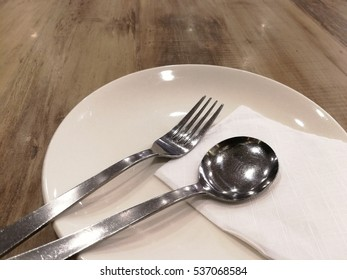 Steel spoon and fork setting in empty white plate with tissue on the wood table.