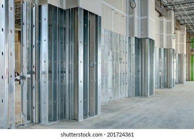 Steel studs used to frame in a large commercial building, with drywall covering.