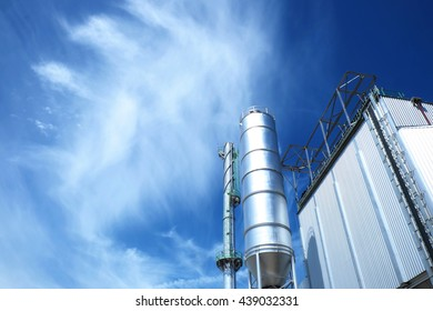 Steel tank/silo with reflective sun light and industrial smokestack with blue cloud sky background.