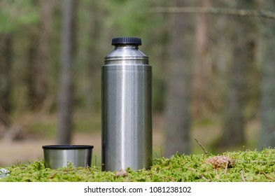 Steel thermos and a mug on a mossy ground in the forest