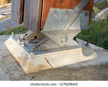 Steel tie joint with swing  beam and anchored into concrete. Modern foot bridge base.