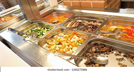 steel trays with plenty of cooked and raw vegetables in the school canteen