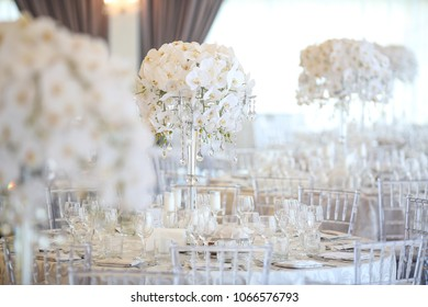 Steel vases with orchids stand on dinner table