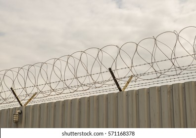 steel wave plate  wall with barbed-wire on cloudy sky background,imprison area