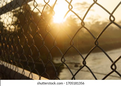 steel wire fence a suspension bridge at sunrise against the background of the river and trees. close up and blurry