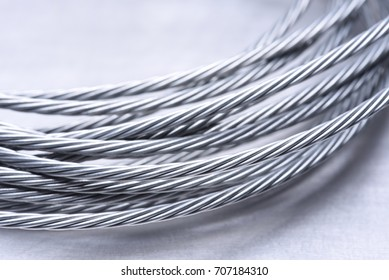 Steel wire rope closeup on grey metal surface