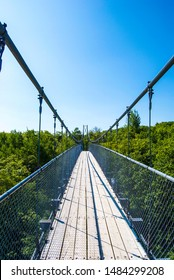 Steel and wood suspension bridge on a bright summer day (Collingwood, Canada)