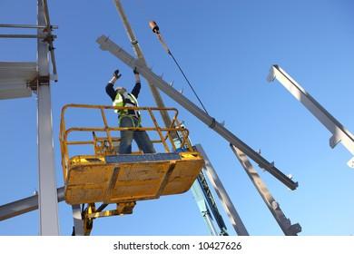 Steel worker on cherry picker.