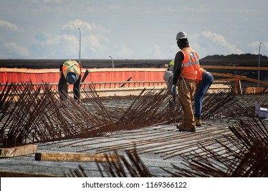 Steel workers on a bridge deck installing  the reinforcing steel bars on top of concrete deck panels and weaving and tying the deck panel reinforcing wire onto the studs welded to the steel girders