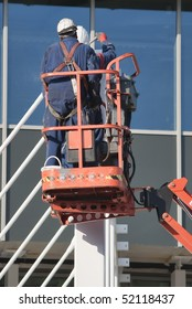 Steel workers wearing safety harness on a cherry picker