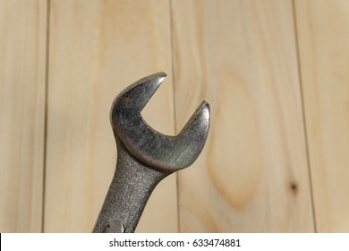 steel wrench tool with wood texture background.