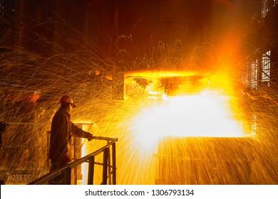 Steelmaker at ingot casting. Electric arc furnace shop EAF. Metallurgical production.