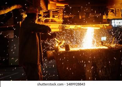 Steelmaker at ingot casting. Electric arc furnace shop EAF. Metallurgy.