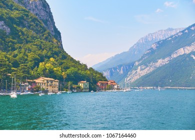 Steep alpine banks of beautiful lake Como with parked boats and yachts near village of Pare, Lombardy, Italy