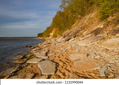 Steep bank and pine forest on the beach of the Baltic Sea coastline, Estonia. Colorful sunset time.