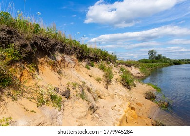 Steep bank of the river with leaning trees and snags near the water. Steep sandy Bank of a forest river with tree roots. Snags and fallen trees on the steep bank of the river.