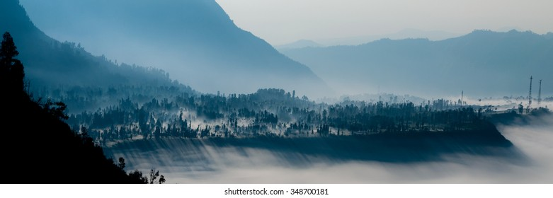 Steep black mountain silhouette in front of thick Fog and cold mist of volcano Bromo in Indonesia
