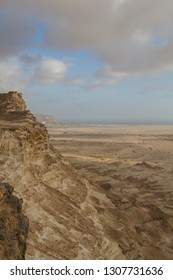 Steep cliffs and dramatic clouds over a plain viewed from a plateau near the coastline in the sultanate of Oman