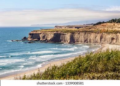 Steep cliffs jut into the Pacific Ocean north of Tunitas Creek Beach near Half Moon Bay with Pillar Point and Mavericks Beach on the horizon in San Mateo County, California.